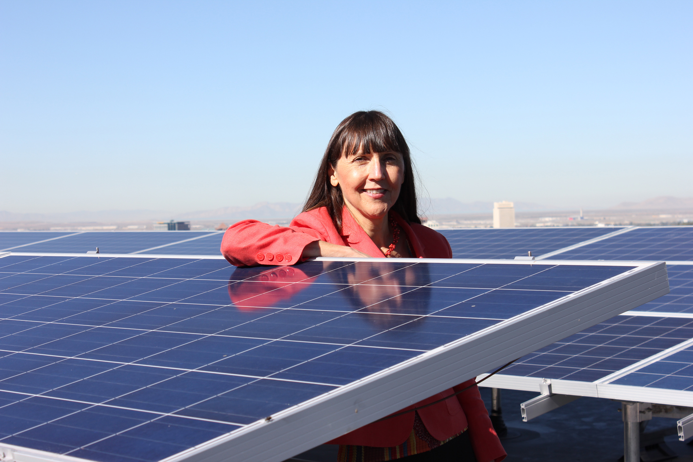 Alberta Comer, dean of the J. Willard Marriott Library and university librarian, poses next to one of the six solar arrays on the library roof.