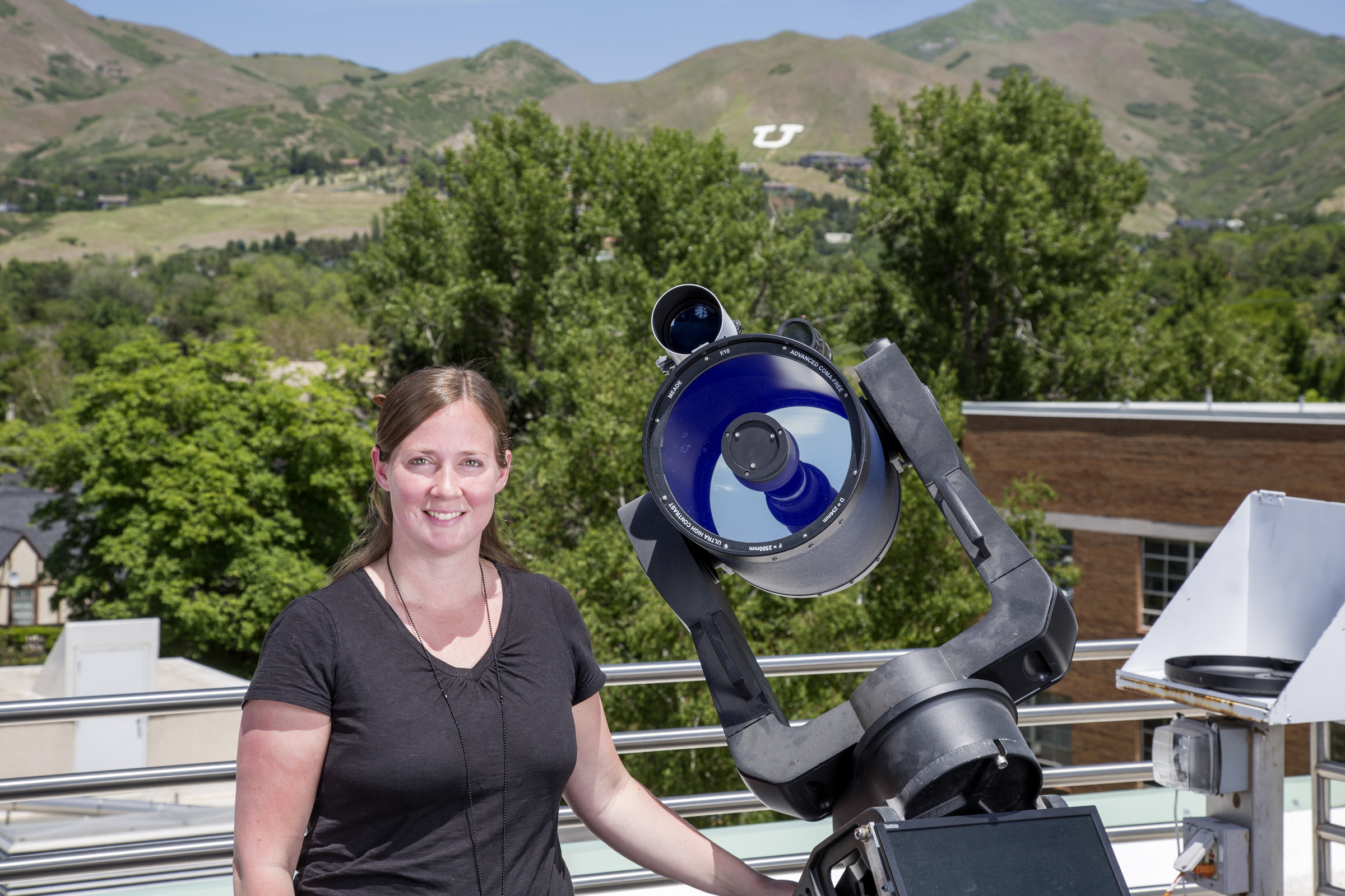 """Tabitha Buehler, Assistant Professor (Lecturer). Coordinator of the new outreach center and head the AstronomUrs outreach team, next to one of five Meade 10"""" LX200 ACF telescopes also available at the South Physics Observatory."""