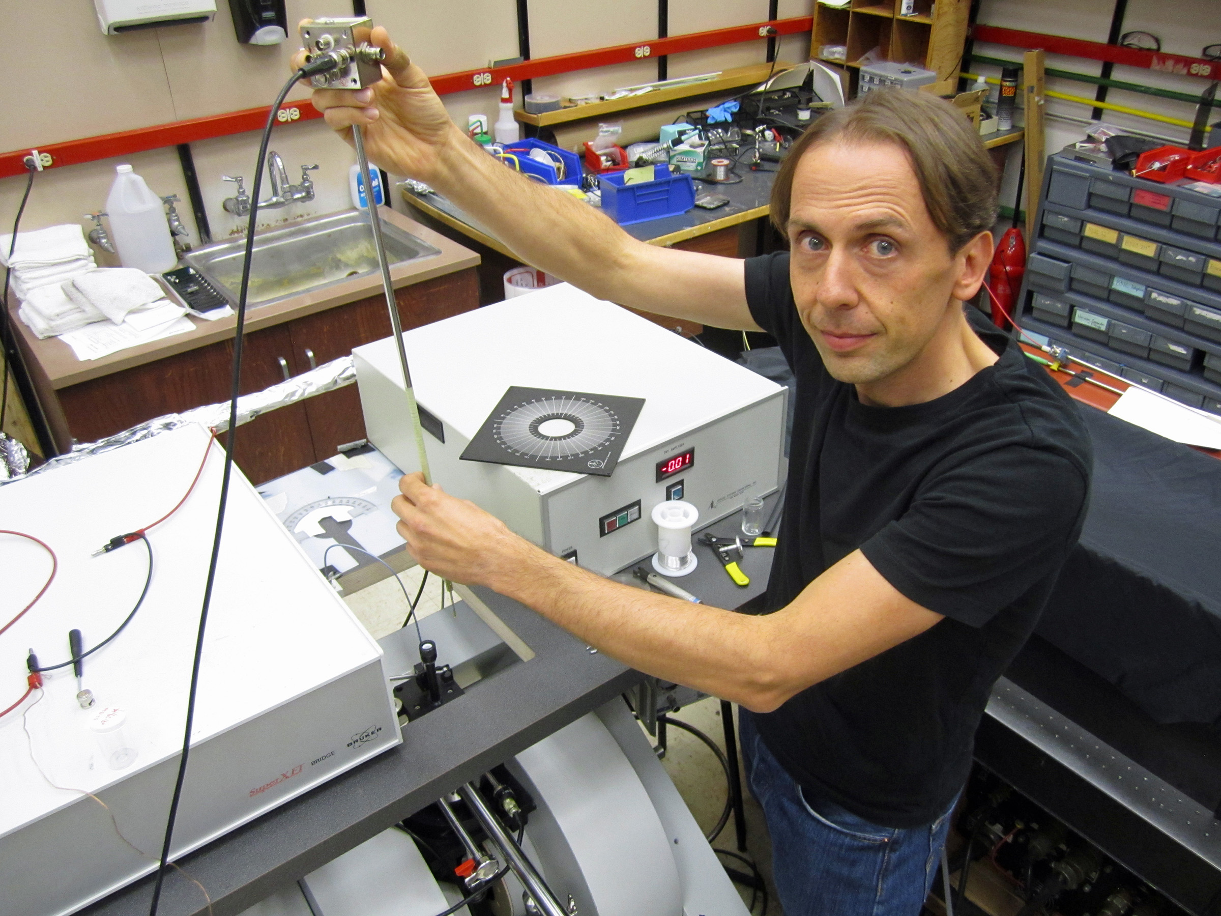 """University of Utah physicist Christoph Boehme works in his laboratory on an apparatus used in a new study that brings physics a step closer to """"spintronic"""" devices such as superfast computers, more compact data storage devices and more efficient organic LEDs or OLEDS than those used today for display screens in cell phones, computers and televisions. The study, published in the Sept. 19 issue of the journal Science, showed the physicists could read the subatomic """"spins"""" in hydrogen nuclei and use the data to control current that powers light in a cheap, plastic LED, or OLED, under practical operating conditions."""
