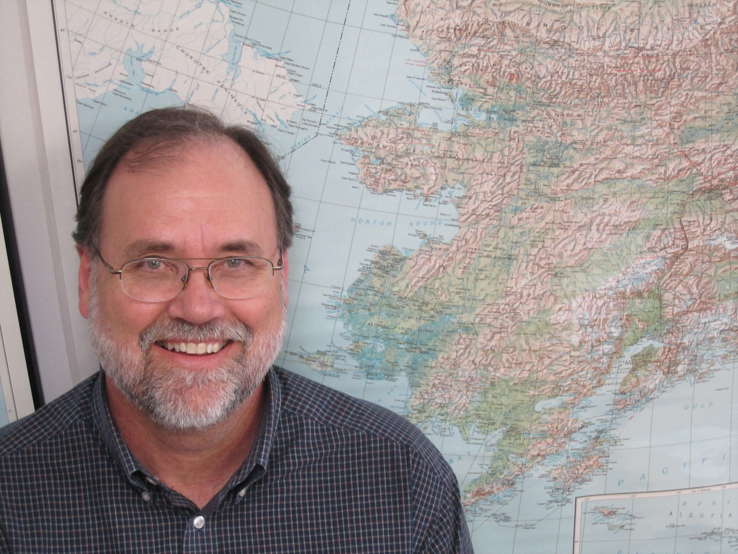 """University of Utah anthropologist Dennis O'Rourke co-authored a Perspective column in the journal Science arguing that genetic, ancient environmental and archaeological evidence can be reconciled in support of the idea that the ancestors of Native Americans spent some 10,000 years living in brushy refuges on the Bering Land Bridge en route from Siberia to the Americas. Contrary to common misperception, the """"bridge"""" really was a landmass 1,000 miles wide from north to south and covered most of the area now shown as ocean on the map around, behind and above O'Rourke's head."""