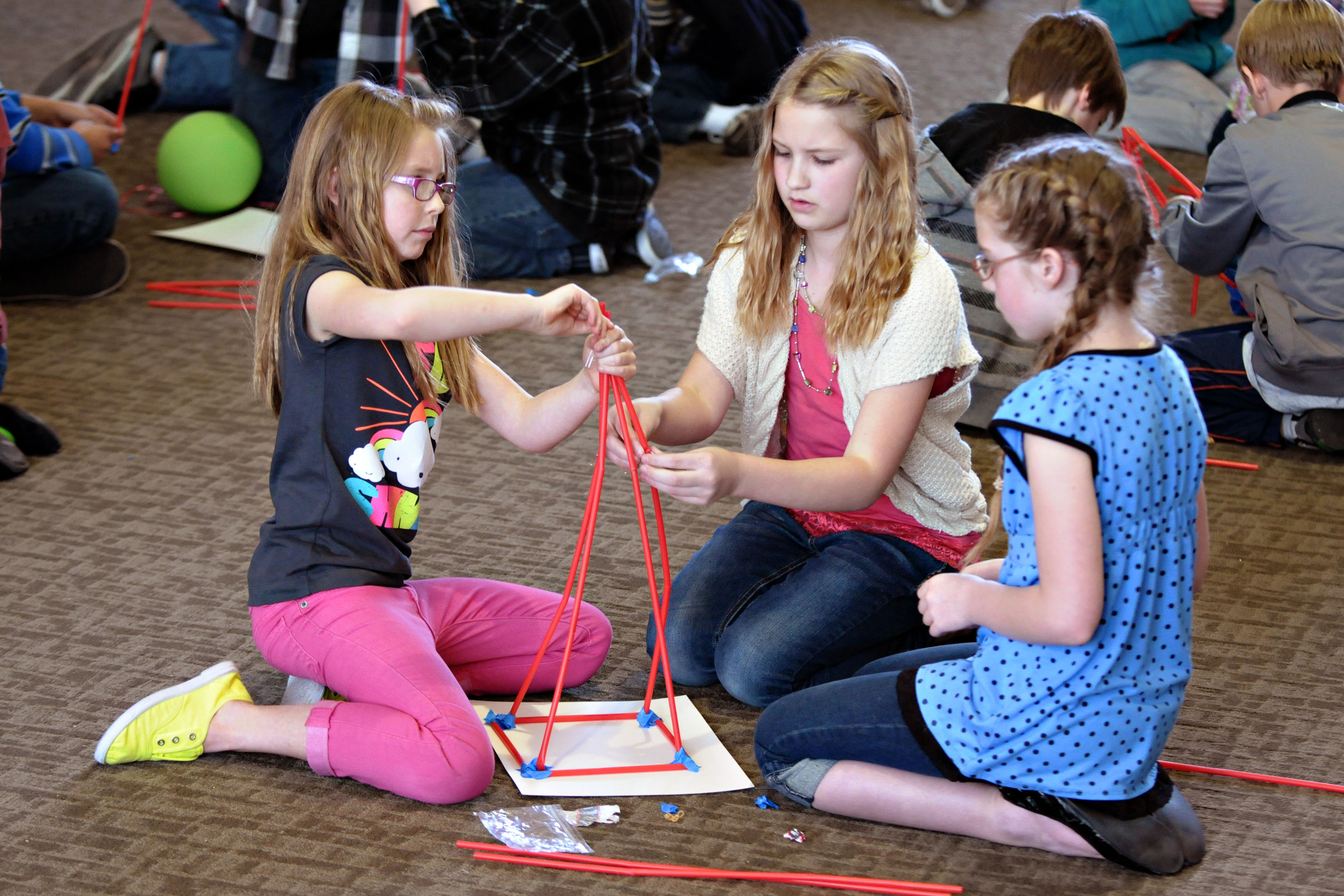 Three elementary school students use drinking straws to build tall towers that can withstand wind gusts during 2012's Elementary Engineering Week at the University of Utah. This year's event takes place March 25-29.