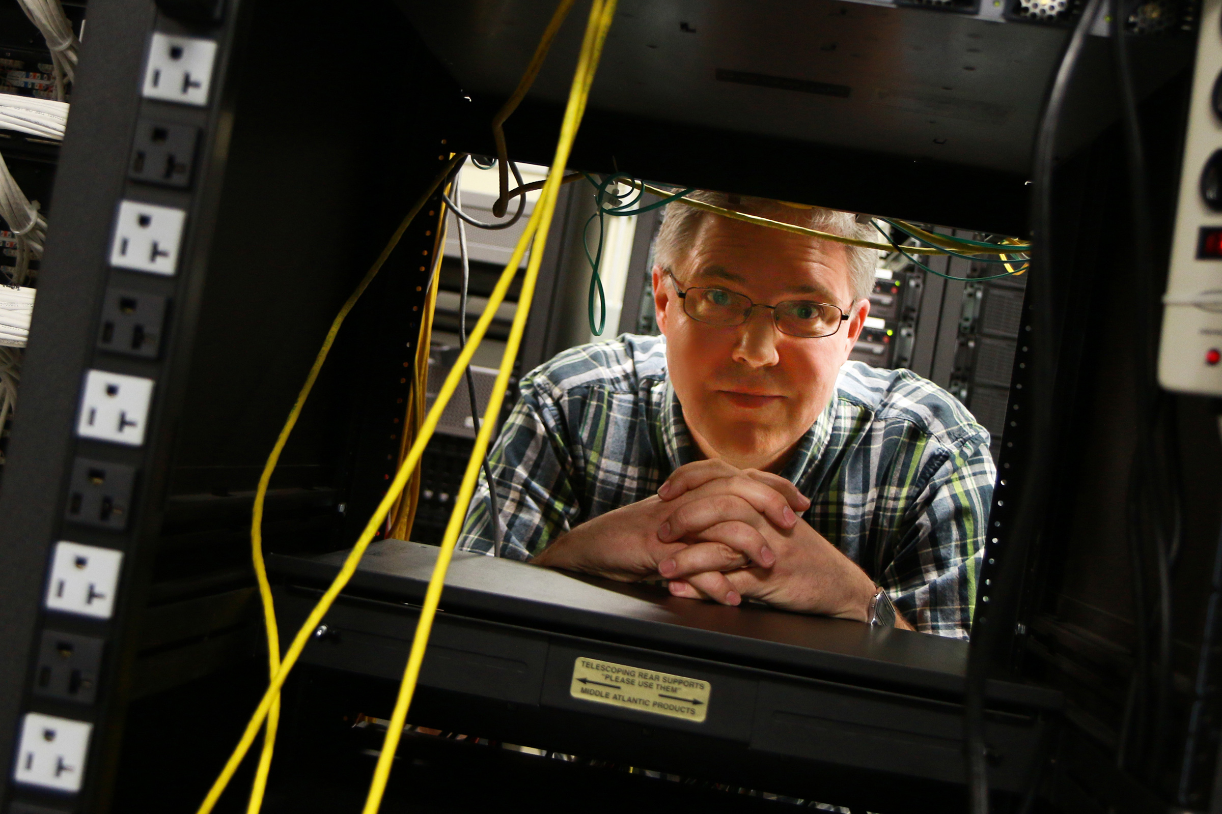 """Eric Eide, University of Utah research assistant professor of computer science, stands in the computer science department's """"Machine Room"""" where racks of web servers sit. It is on these computers that Eide, U computer science associate professor John Regehr, and their research team created and tested A3, a suite of computer applications that defeat malware and automatically repair the damage it causes. The project could help lead to better consumer software defenses."""
