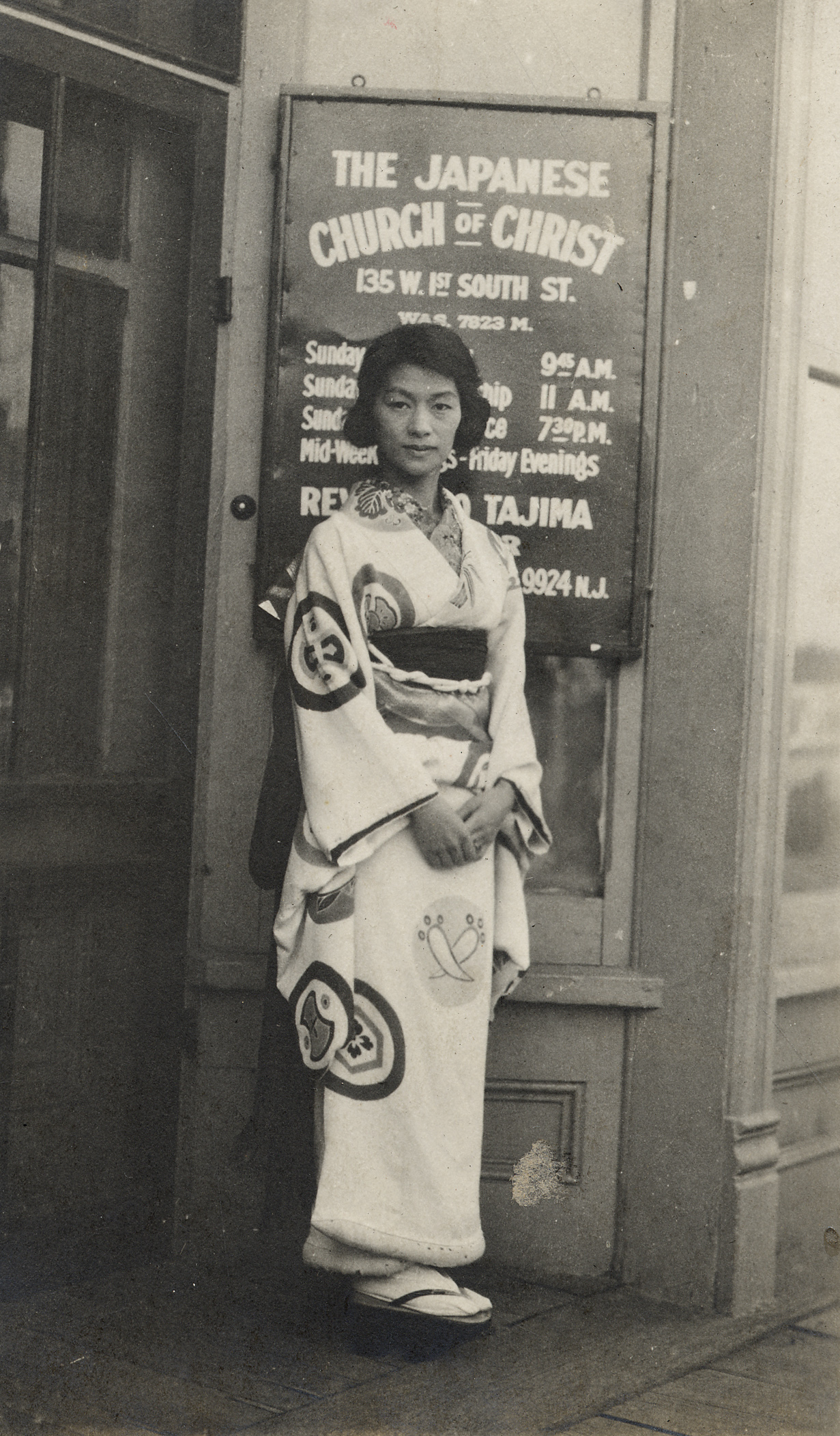 An unidentified woman stands in front of the original location of the Japanese Church of Christ in Salt Lake City's Japantown, circa early 1920's.
