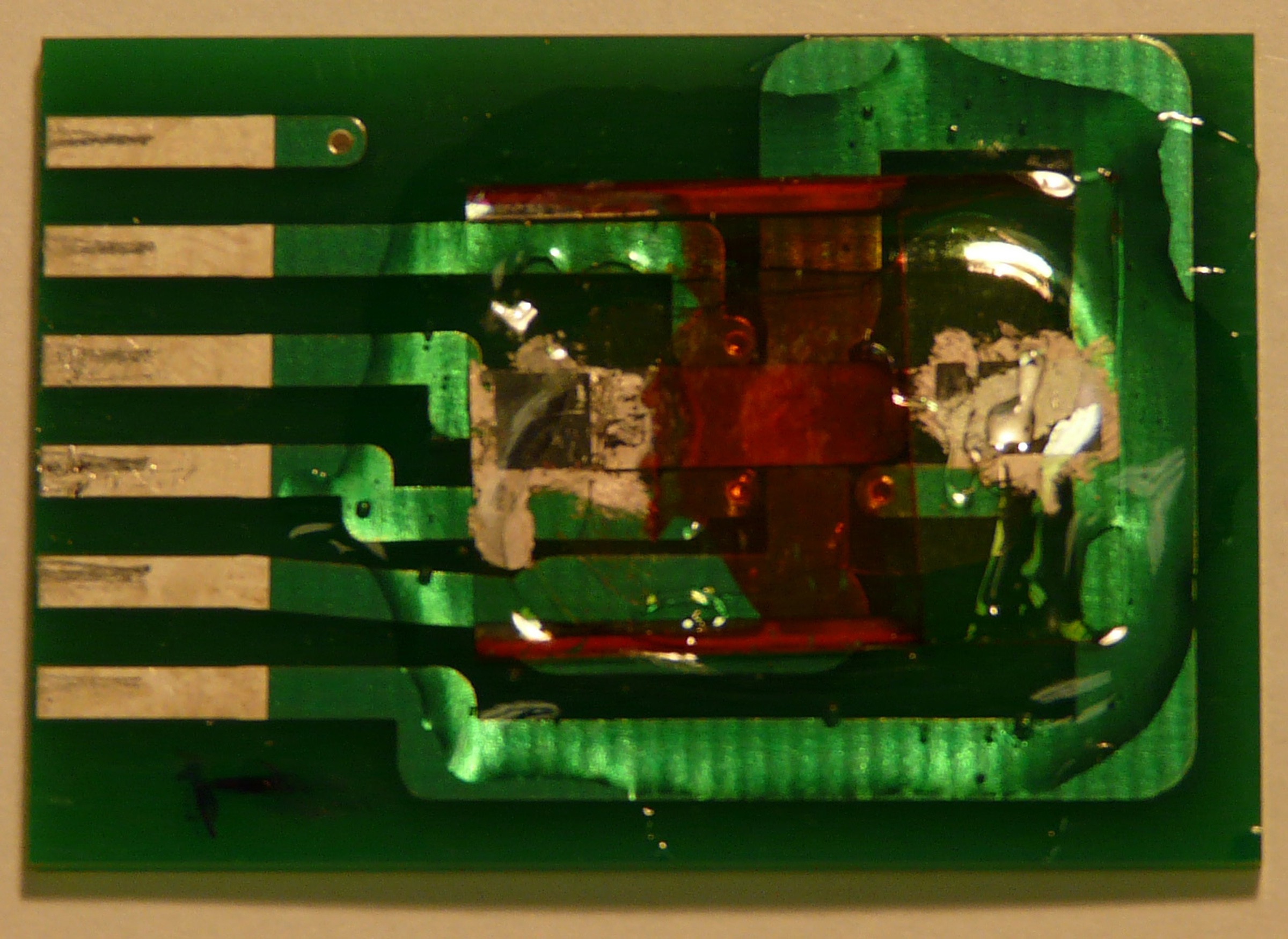 """An inexpensive and highly accurate """"spintronic"""" magnetic field sensor developed at the University of Utah is shown here. The entire device, on a printed circuit board, measures about 0.8 inches by 1.2 inches. But the part that actually detects magnetic fields is the reddish-orange thin-film semiconductor – essentially """"plastic paint"""" – near the center-right of the device."""