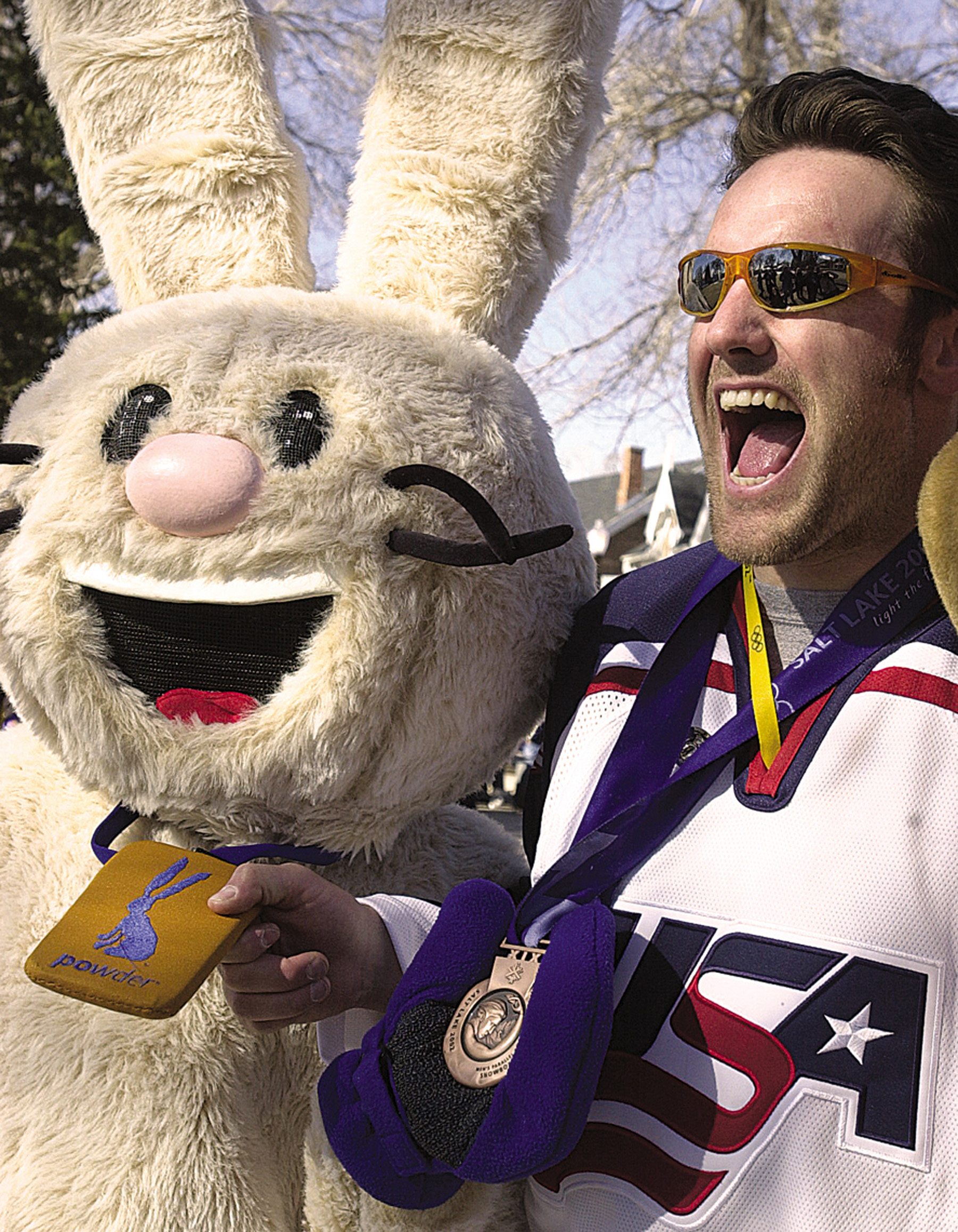Powder poses with an athlete during a celebration at the Olympic Village.