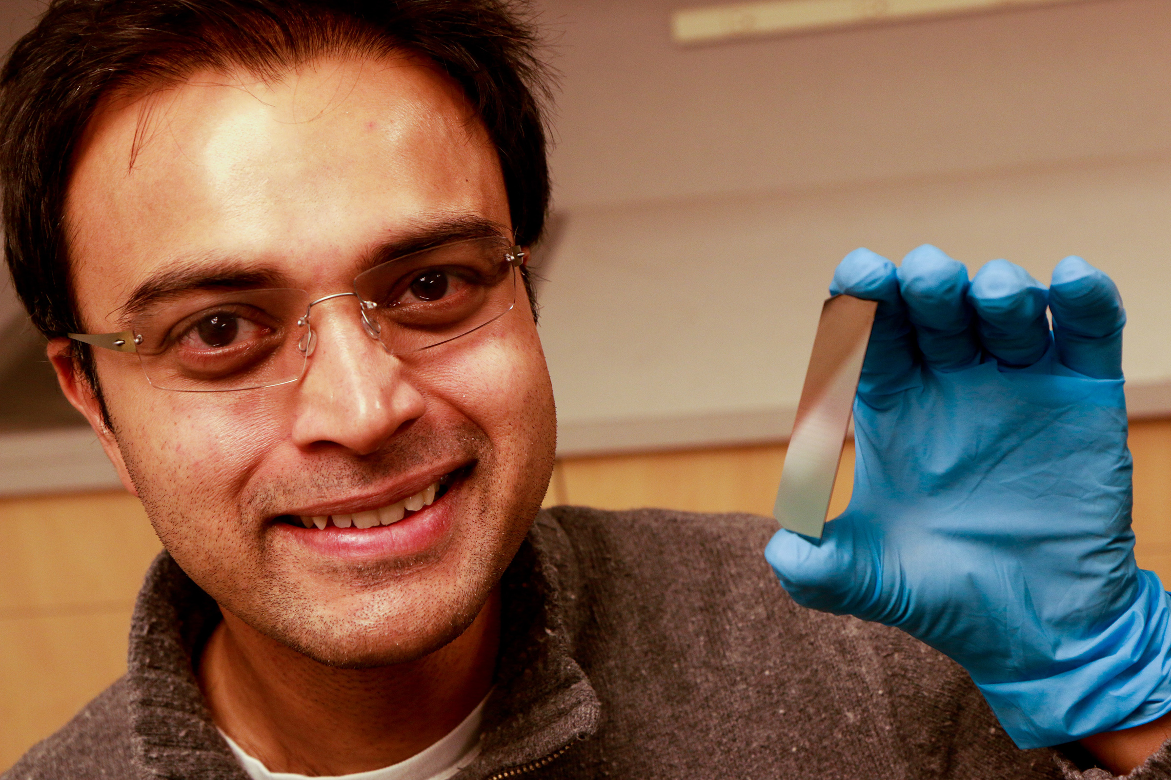 University of Utah electrical and computer engineering associate professor, Rajesh Menon, holds up a piece of silicon that has been etched with microscopic pillars and holes to create a polarized filter. He leads a team of researchers that have developed a new polarizer that can allow more light to pass through than conventional polarizers. This could lead to LCD displays for smartphones and tablets that last longer on a battery charge and cameras that can take better pictures at low light.