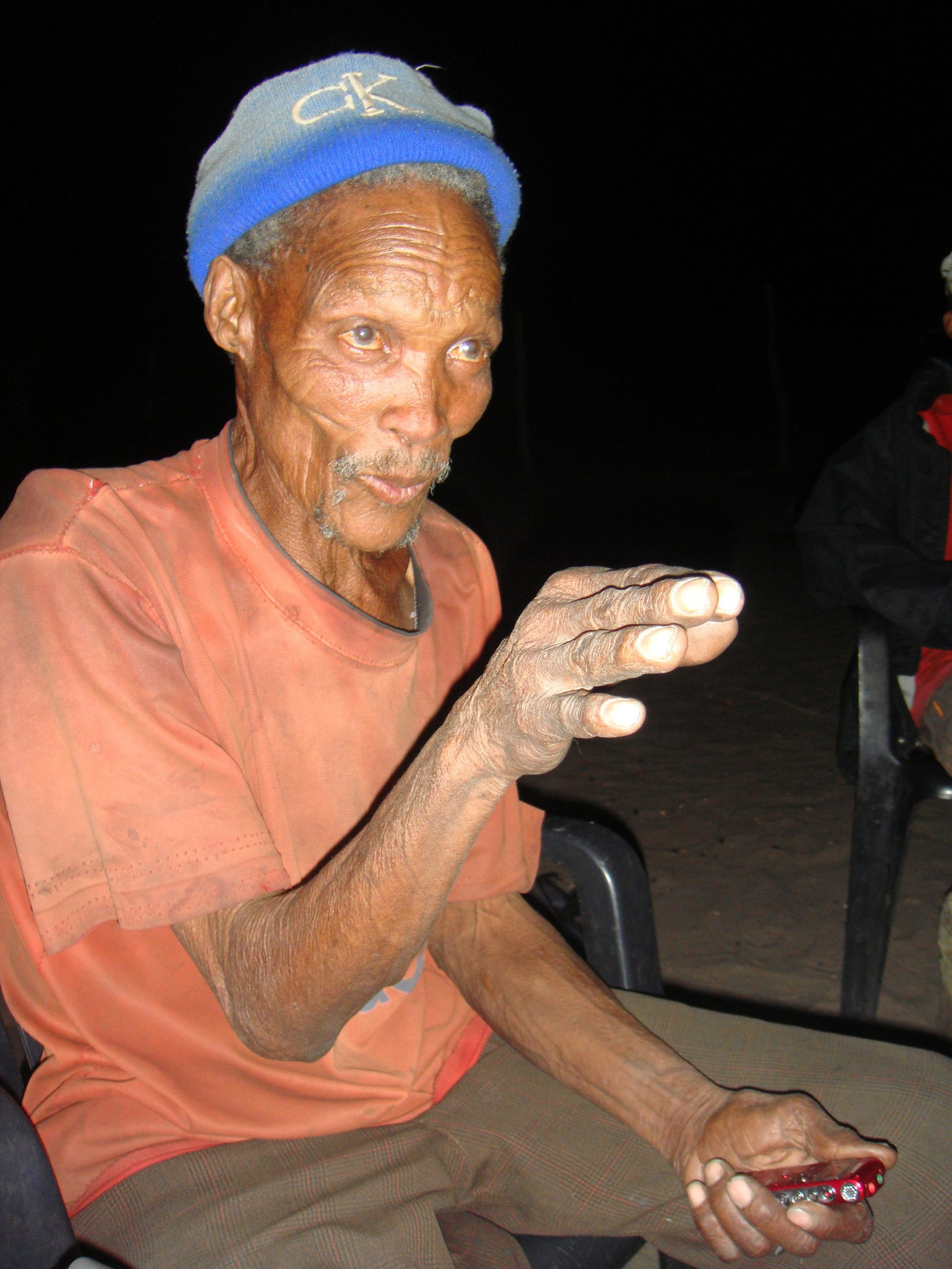 A !Kung Bushman, sporting a Calvin Klein hat, tells stories at a firelight gathering in Africa's Kalahari Desert. University of Utah anthropologist Polly Wiessner has published a new study of the Bushmen suggesting that when firelight extended the day for human ancestors, stories told around the campfire helped stimulate human mental, social and cultural development.