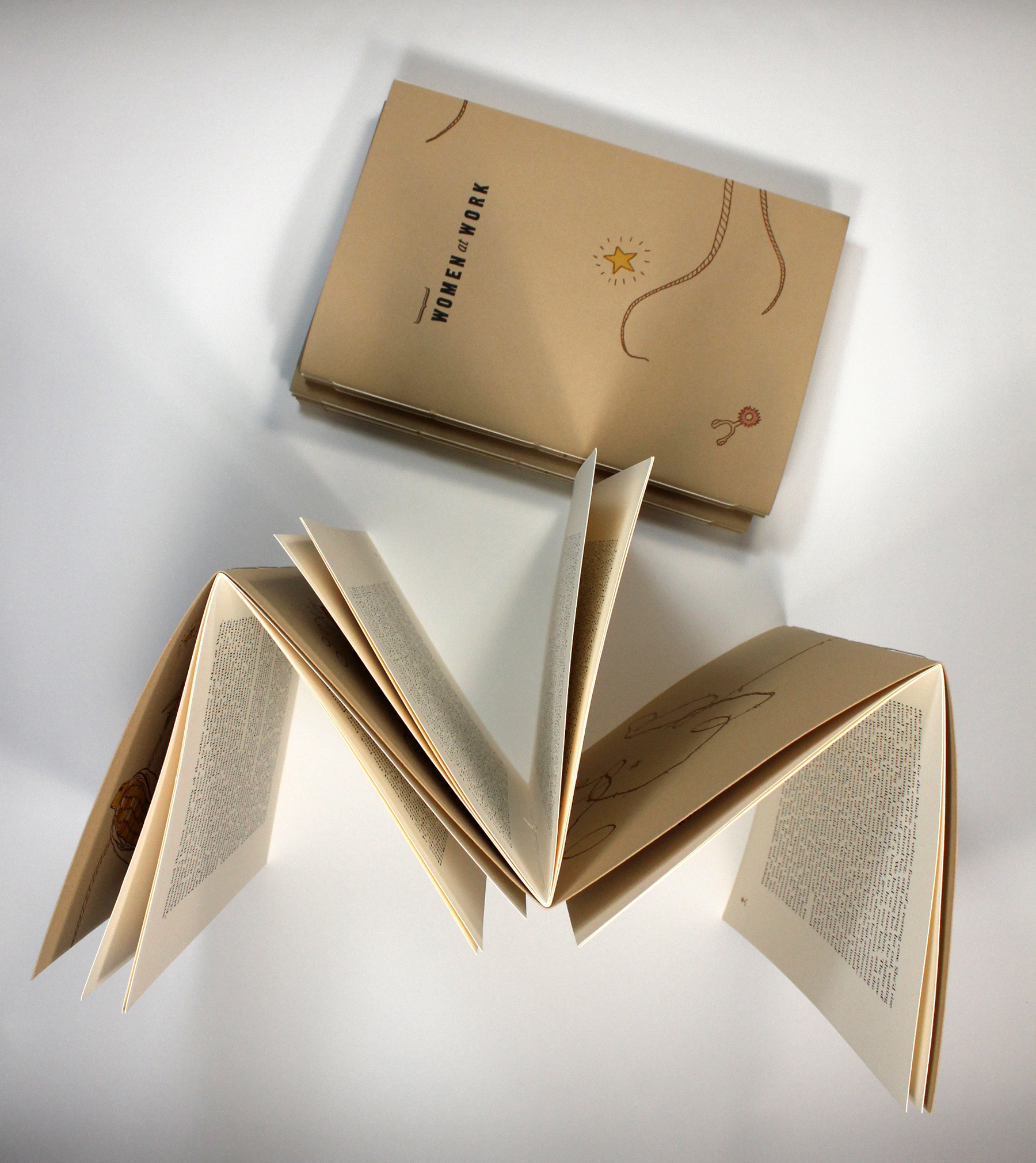"""Hand-crafted copies """"Wo/Men at Work"""" produced by the University of Utah's, Book Art program."""