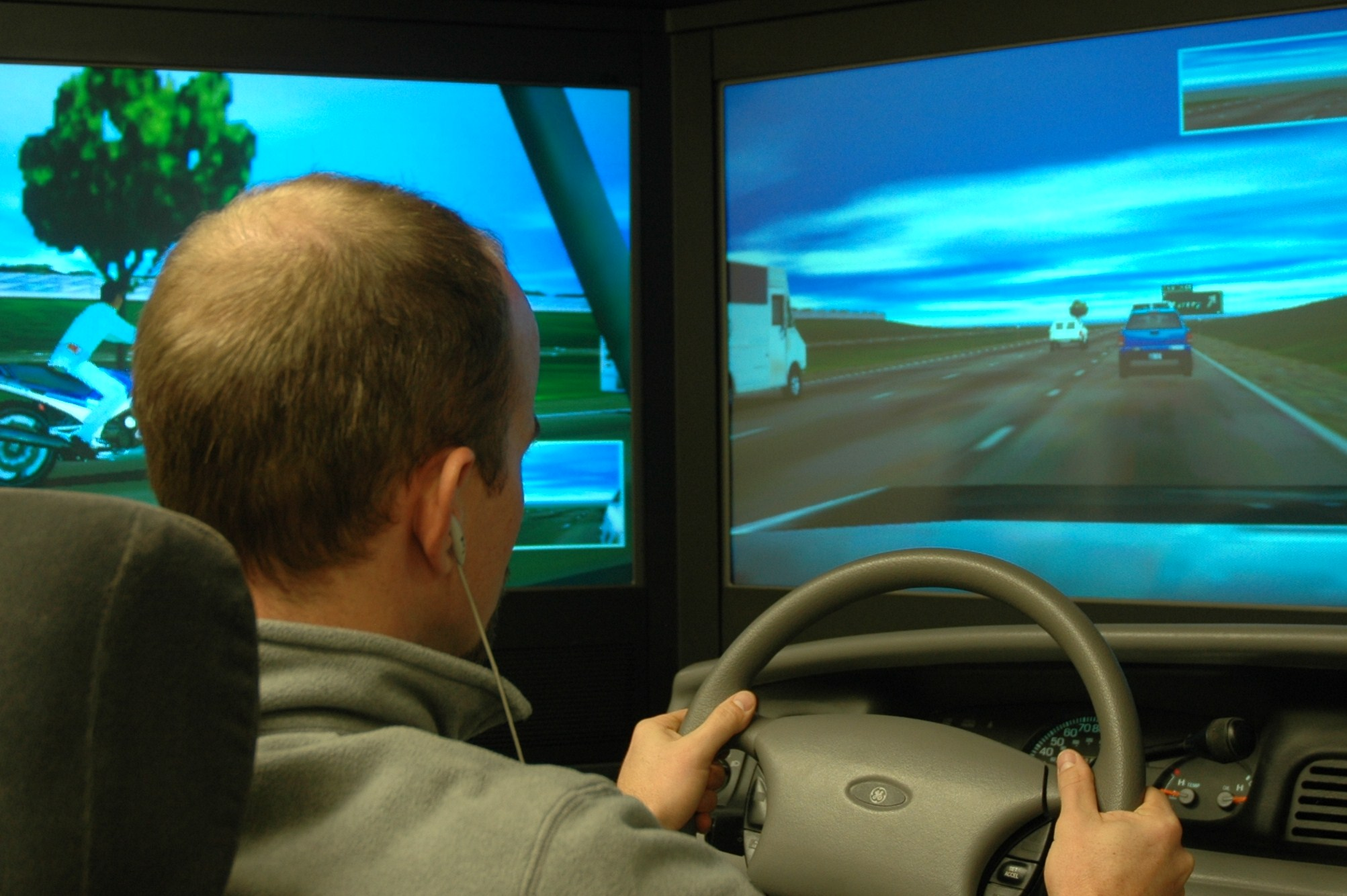 Joel Cooper, a University of Utah doctoral student in psychology, demonstrates how subjects in a new study talked on a cell phone while operating a driving simulator. The new Utah study found that motorists on cell phones contribute to traffic congestion because they drive slower and are less likely to pass slow-moving vehicles.