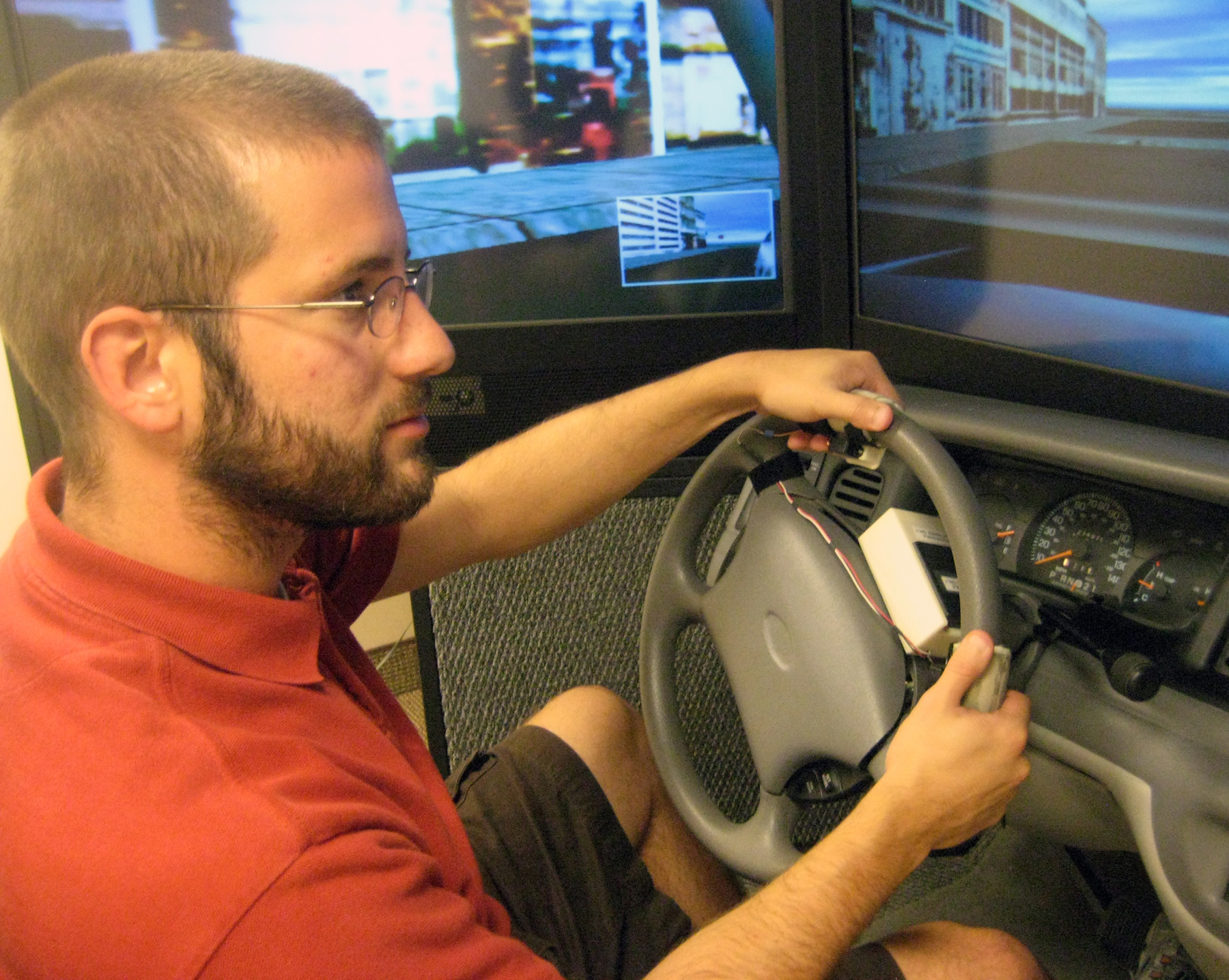 Nate Medeiros-Ward, a University of Utah psychology doctoral student, operates a driving simulator with a steering wheel equipped with two touch devices that pull the skin on his index fingertips left or right (counterclockwise or clockwise) to tell him which way to turn. A new University of Utah study found that navigation information can be conveyed to a driver through the fingertips as accurately as through audio instructions from a navigation system. And when drivers are distracted by talking on a cell phone, the fingertip instructions are followed more accurately than audio instructions. The touch-based devices could help improve safety for motorists and hearing-impaired drivers, and also lead to navigational canes that provide navigation information to blind pedestrians.