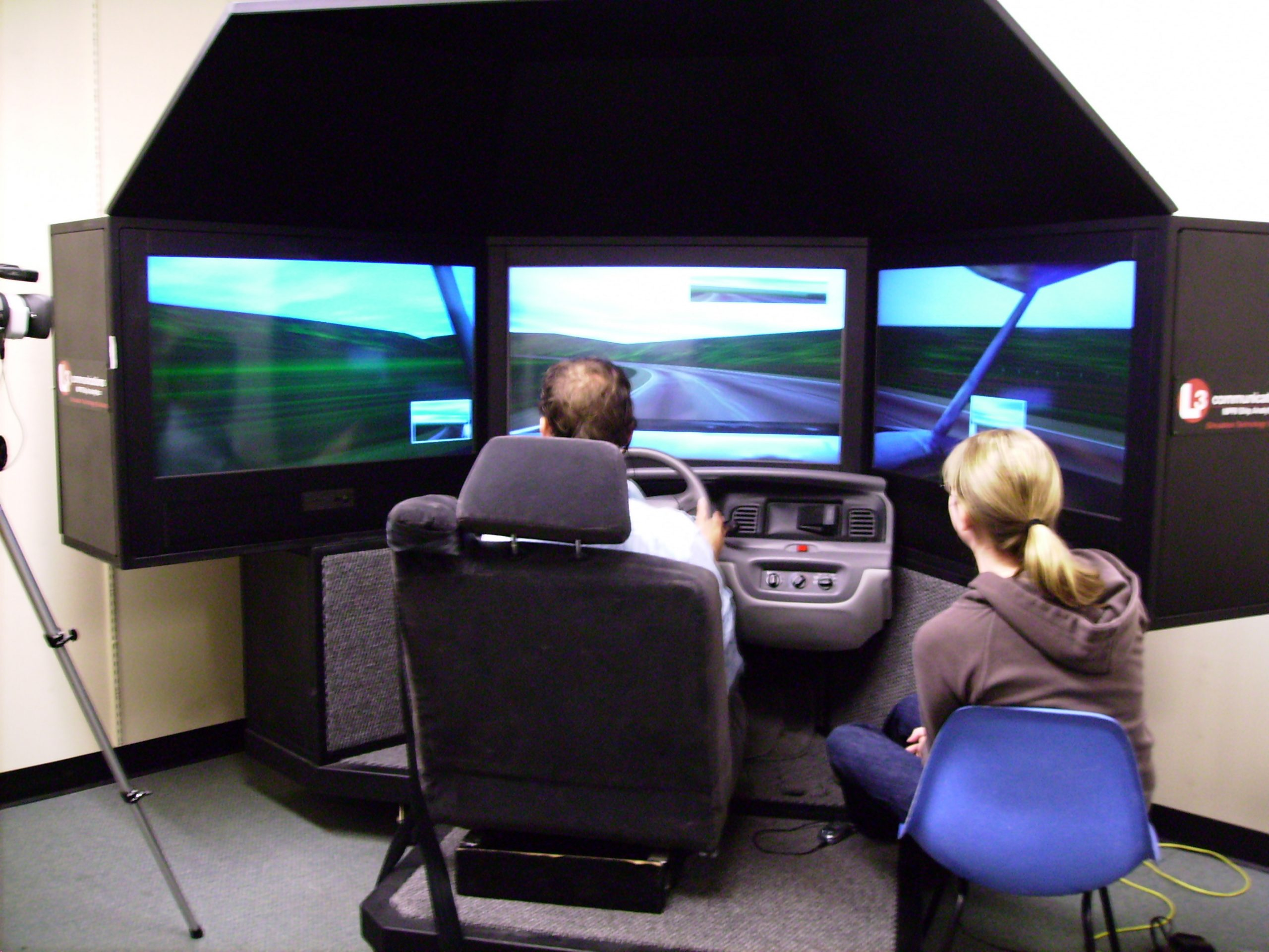 University of Utah psychology graduate students Russ Costa and Janelle Seegmiller demonstrate the driver and passenger roles used by participants in a study of how drivers are affected by conversations with passengers versus conversations over a cell phone. The study, which used the sophisticated driving simulator shown in the photo, found that when drivers talk on cell phones, they are more likely to drift out of their lane and miss exits.