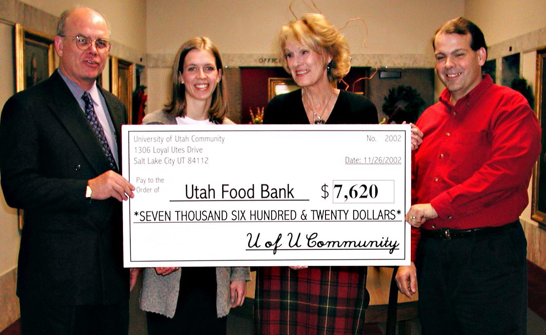 President Machen, John Fackler and Jessica Judkins present check to Utah Food Bank representative