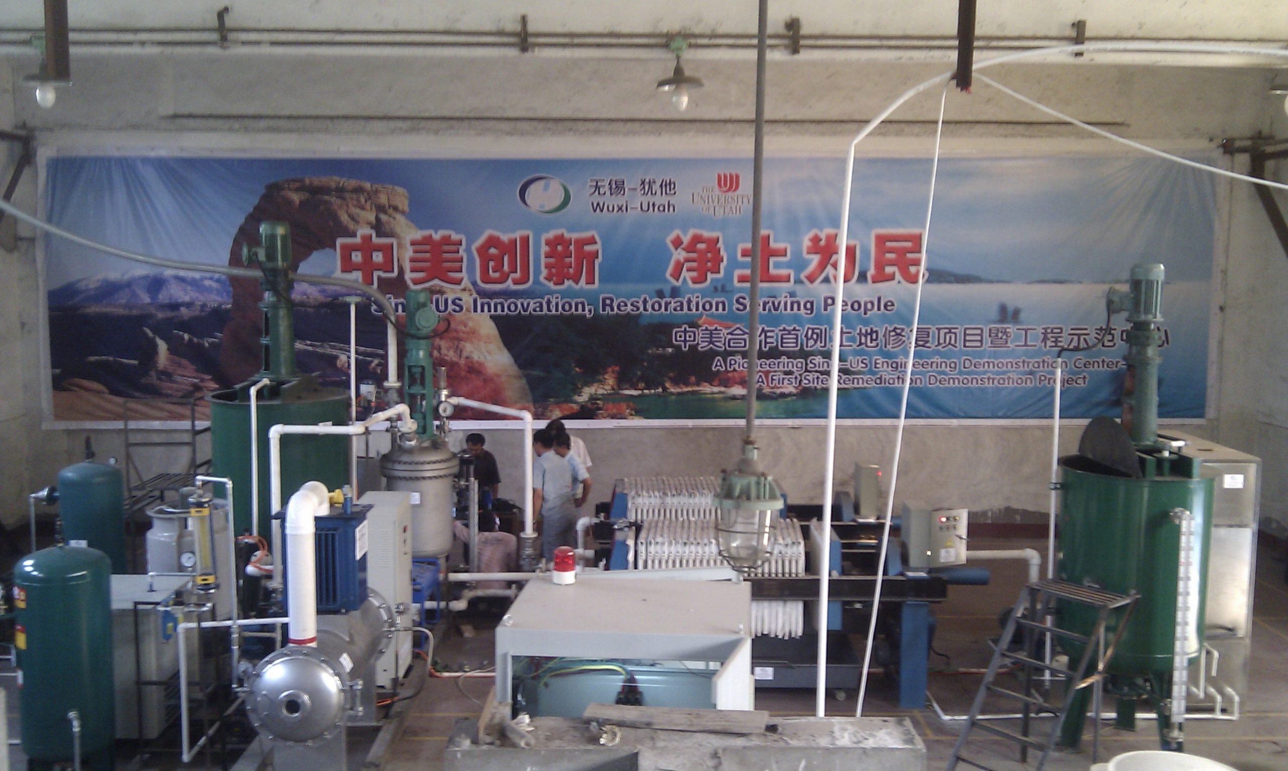University of Utah civil and environmental engineer Andy Hong has teamed up with Chinese environmental cleanup company Honde LLC to use Hong's method of heightened ozonation treatment or HOT to clean metals and other contaminants from polluted soil along the shores of Lake Taihu near Wuxi, China. The treatment system at Lake Taihu is shown in this photo. The HOT reactor or vessel where ozone treatment occurs is the vertical, silver-colored tank left of center. It is an essential component in the treatment system that also includes an ozone generator, compressor, air tank, green mixing tanks, press filter and plumbing.
