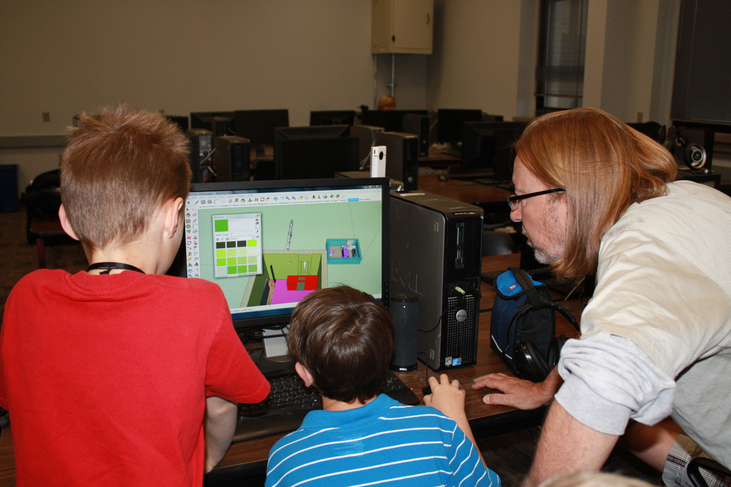 The University of Utah has teamed with Google to teach kids with autism how to use Google's 3D modeling software called SketchUp. A new study from the university shows that in developing the workshops designed to teach needed job skills, Utah researchers found extra benefits, such as stronger interpersonal relationships and greater confidence due, in large part, to a focus on the kids' talents instead of their disorder. Here, certified SketchUp instructor Steve Gross teaches two children how to use the software.