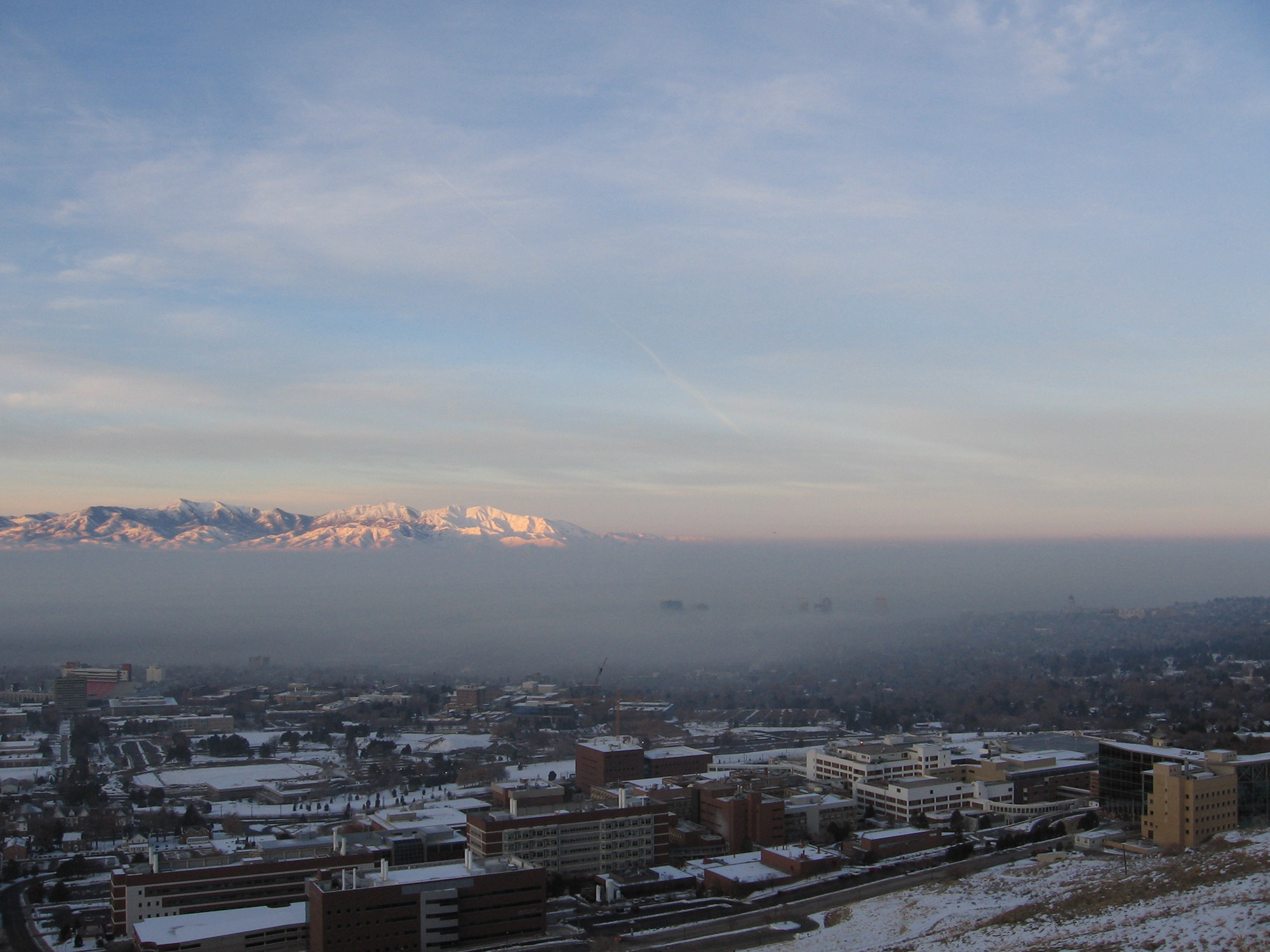 A wintertime inversion or cold-air pool traps air pollution over the Salt Lake Valley, almost completely obscuring downtown Salt Lake City in the center of the photo. The University of Utah campus sprawls in the foreground, on the city's east bench and mostly above the inversion. The University of Utah will lead a $1.3 million study aimed at better understanding conditions that lead to the formation, maintenance and breakup of the polluted inversions.