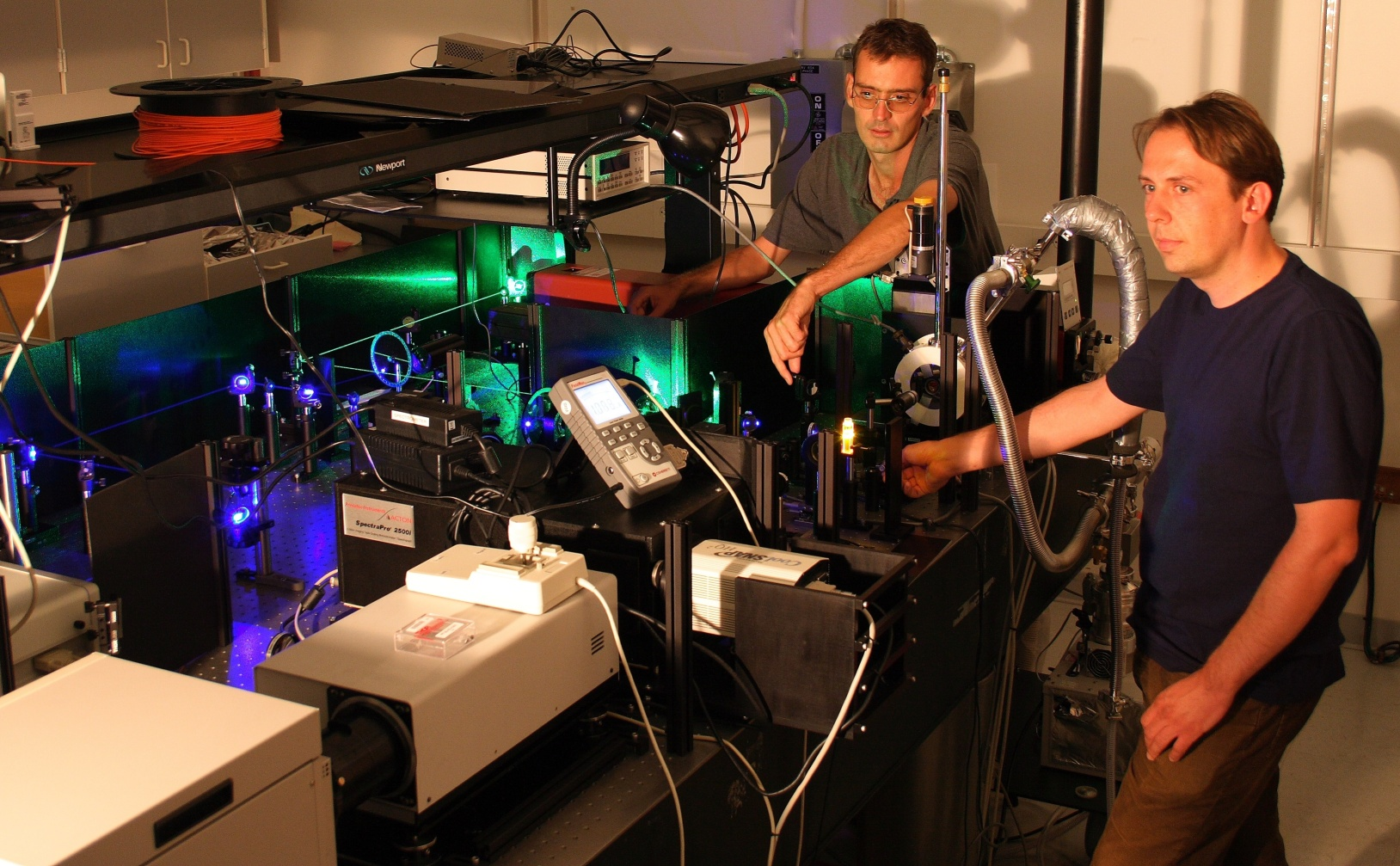 """University of Utah physicists John Lupton and Christoph Boehme use green and blue laser beams to """"excite"""" a small piece of an organic or """"plastic"""" polymer (glowing orange near Boehme's right hand) that may serve as a light-emitting diode (LED) for computer and TV displays and perhaps lighting."""