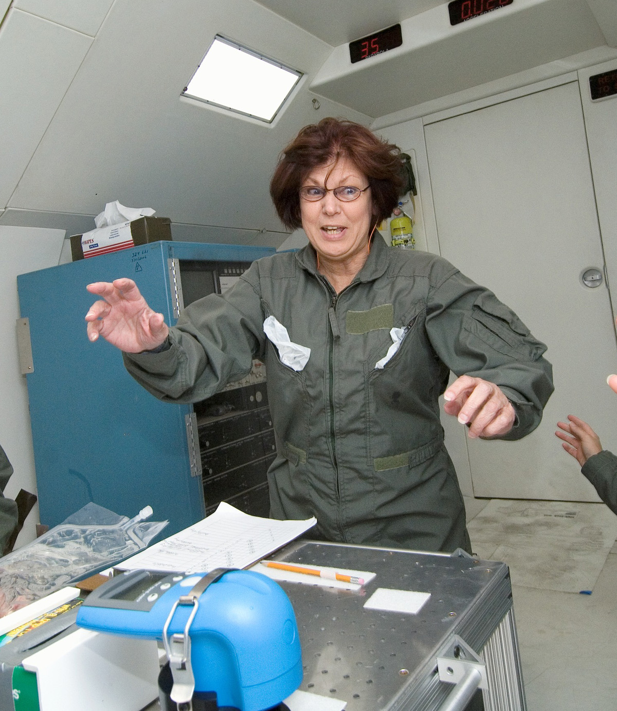 """University of Utah chemist Lorraine Siperko experiences weightlessness during a flight aboard a NASA """"vomit comet"""" aircraft. Siperko made several such flights to test a new system designed to monitor drinking water quality aboard spacecraft. The system includes a commercially available color sensor (blue device in foreground) that checks the level of disinfectant in drinking water. The water quality monitoring system was delivered to the International Space Station in August for six months of tests."""
