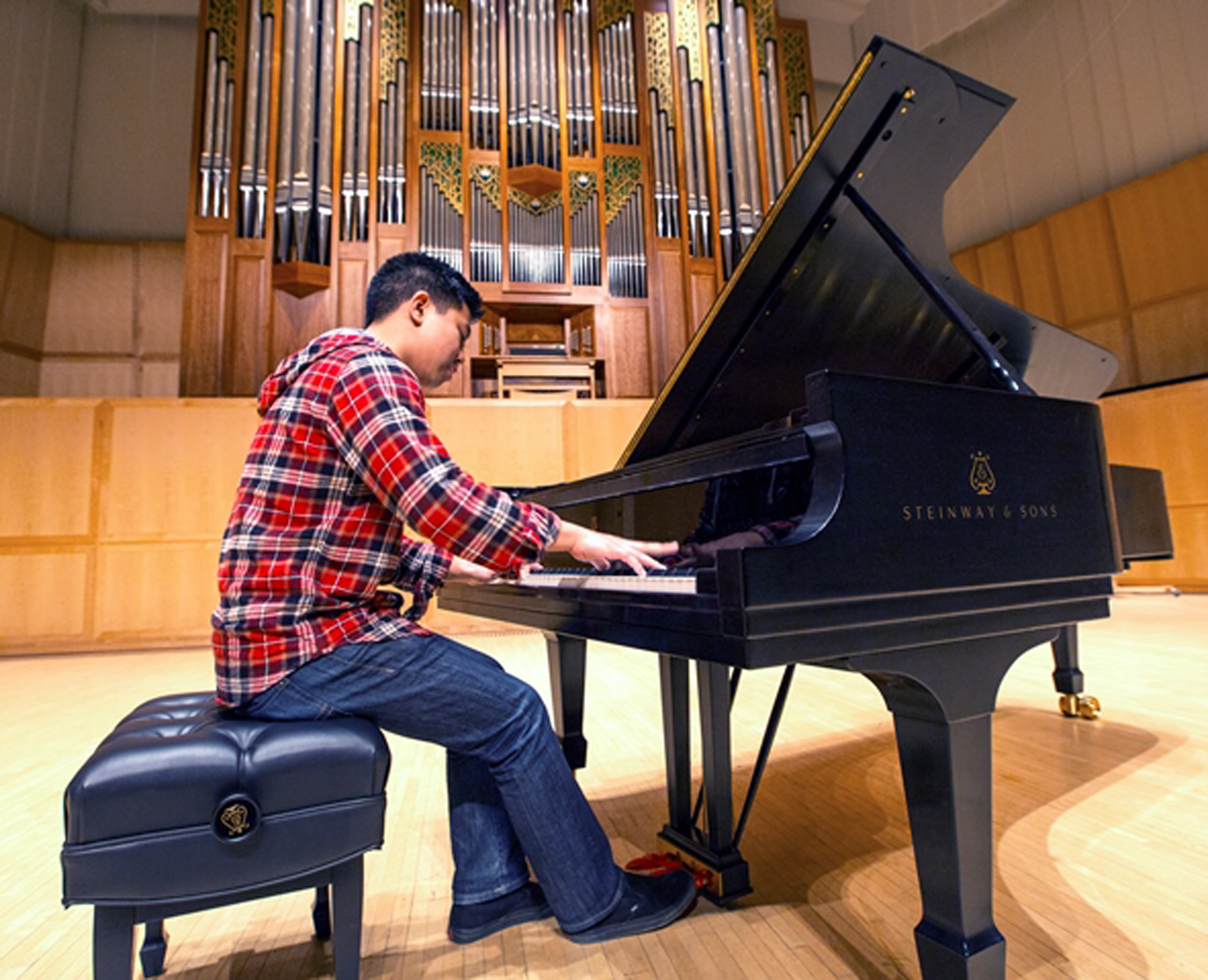 A lucky student is first to play the new Steinway Concert Grand in the Libby Gardner Concert Hall on the U campus.