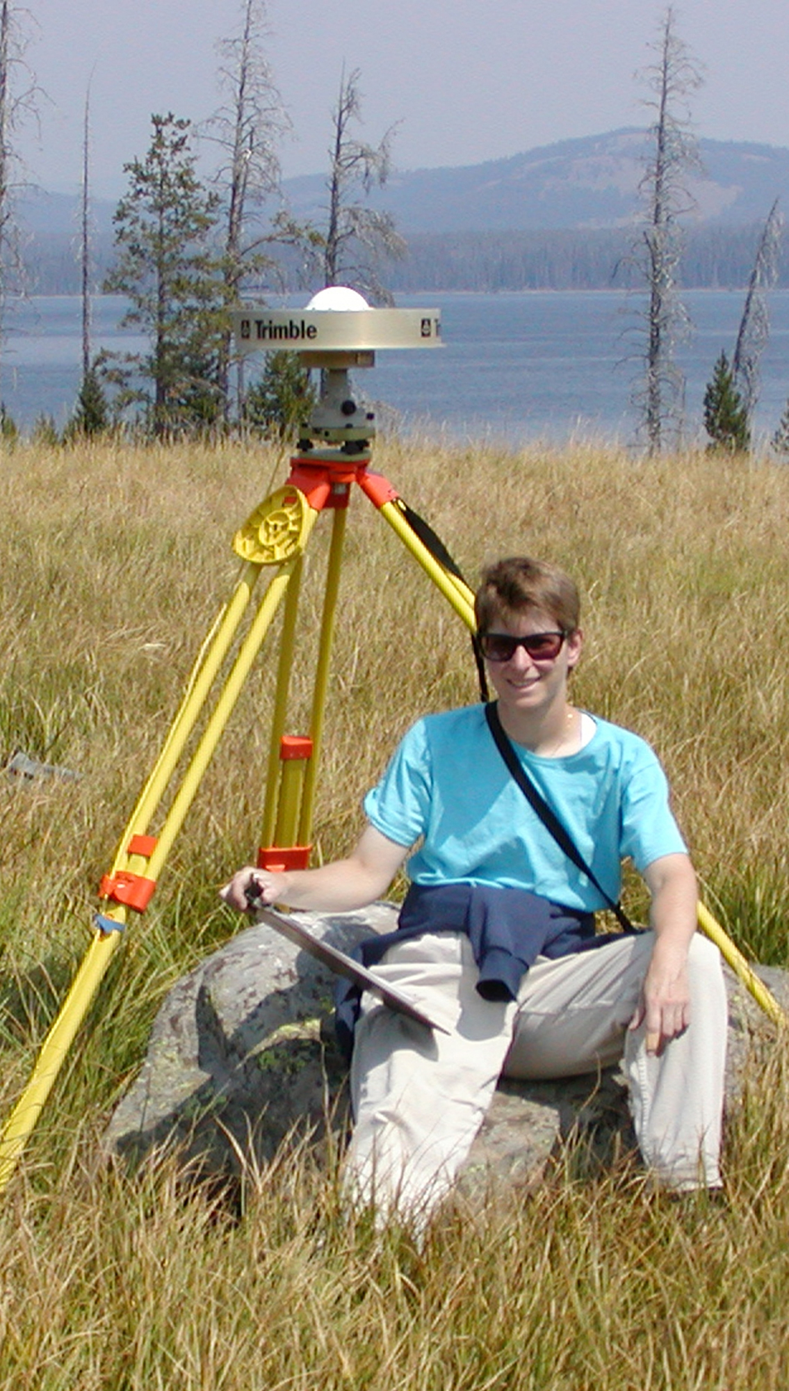 Christine Puskas, a University of Utah doctoral student in geophysics, sits by a portable Global Positioning System (GPS) antenna near the shore of Yellowstone Lake in Wyoming. Puskas, Utah geophysicist Robert B. Smith and others have published a study based on 17 years of GPS measurements showing how Earth's crust in a large region of the West is deformed by the Yellowstone hotspot, a giant plume of hot and molten rock that powers Yellowstone's hot springs and geysers, generates earthquakes and occasionally produces catastrophic volcanic eruptions.