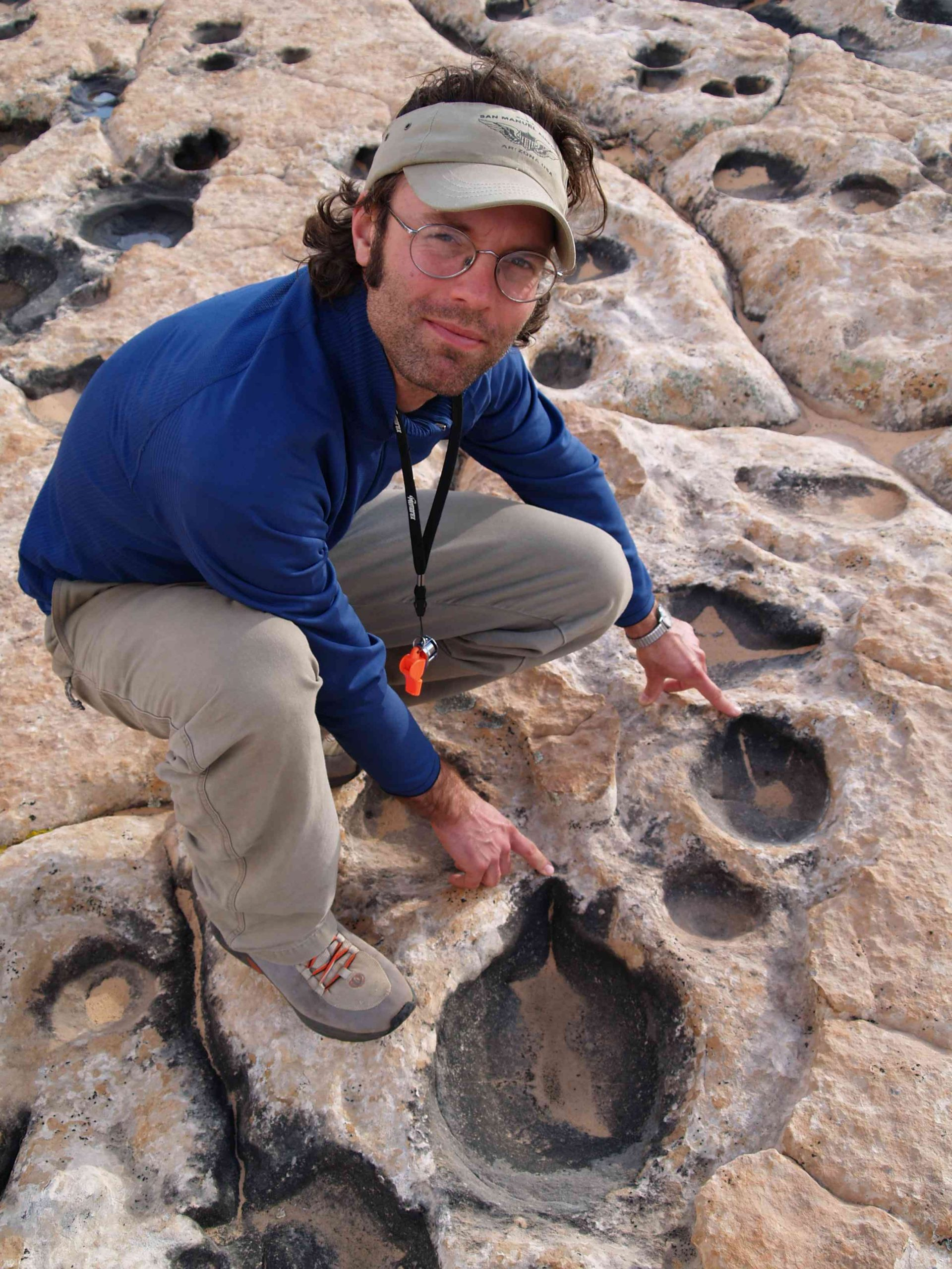 """Geologist Winston Seiler with some of the dinosaur tracks he identified for his thesis as a University of Utah master's degree student. The impressions once were thought to be potholes eroded by water. But Seiler and Marjorie Chan, chair of geology and geophysics at the University of Utah, published a scientific paper in the October 2008 issue of the journal Palaios identifying the abundant impressions as comprising a large dinosaur """"trample surface"""" in northern Arizona. There are so many tracks they wryly refer to the site as """"a dinosaur dance floor."""""""