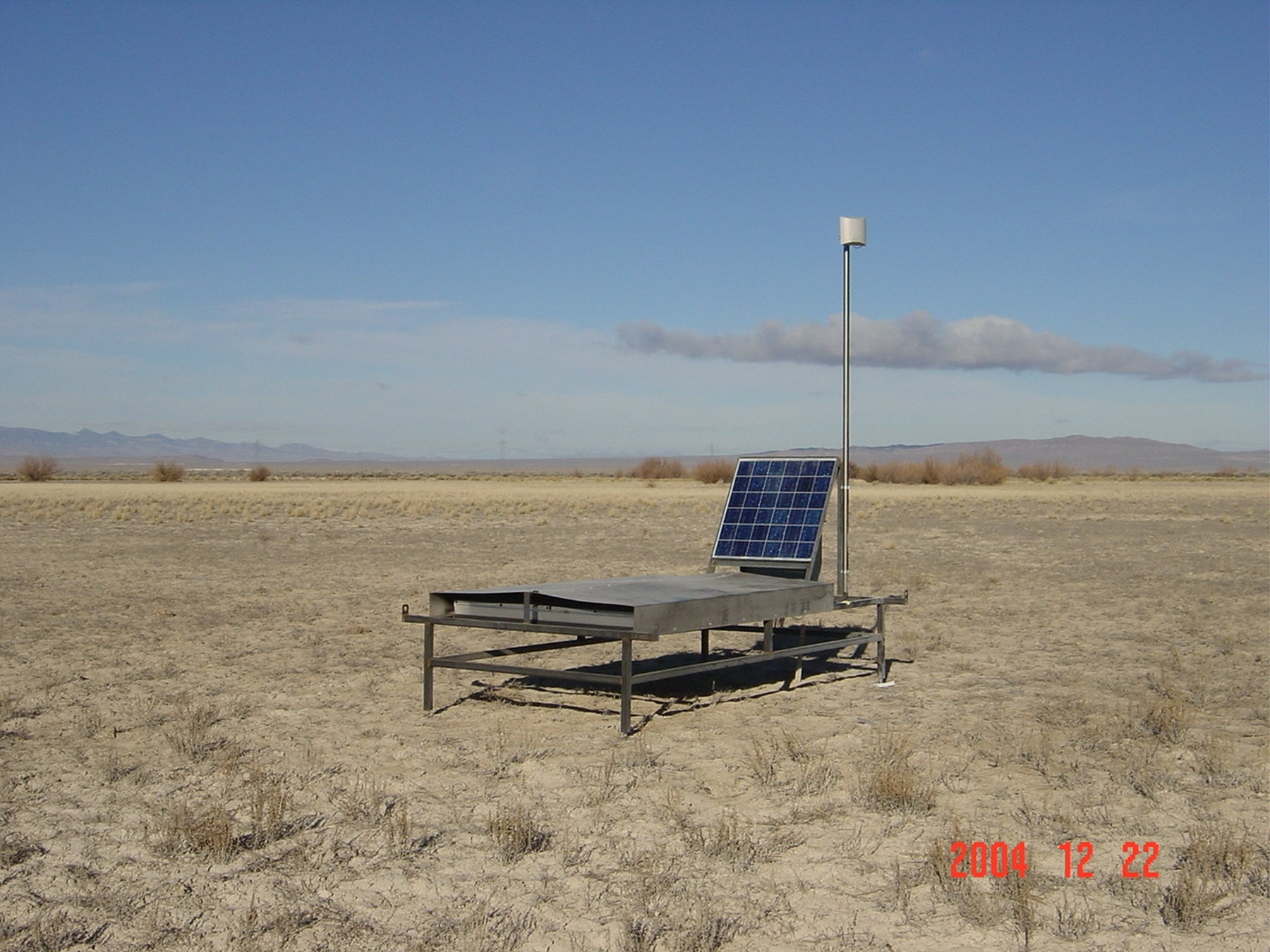 """A table-like scintillation detector sits in the Utah desert, powered by a solar panel. A grid of 564 such devices will be installed in a 400-square-mile area west of Delta, Utah, as part of the $17 million Telescope Array cosmic ray observatory. The scintillation detectors will measure """"air shower"""" particles that hit Earth after incoming cosmic rays smash into gas particles in Earth's atmosphere."""